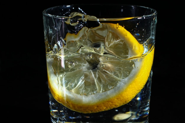 Limão em um copo de água em um fundo preto escuro