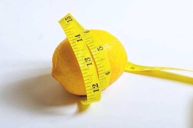 Limão em um fundo branco com uma fita métrica. o conceito de dieta saudável, perda de peso. vitamina c.