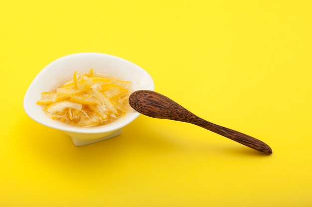 Limão fatiado com mel ou açúcar em uma tigela branca. base para chá de limão ou de ervas.