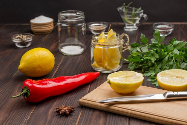 Limão fatiado e faca na tábua. limão na jarra. pimenta, limão inteiro e sal na mesa. fonte natural de fortalecimento da imunidade.