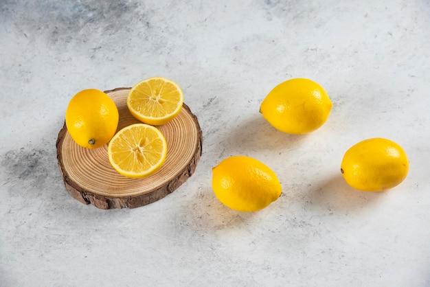 Limão fatiado e inteiro em um fundo de mármore.