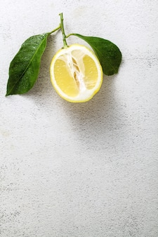 Limão fatiado em uma mesa de pedra branca com folhas.