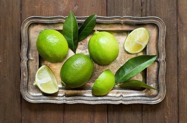 Limão fresco com folhas em uma bandeja de prata em uma vista de mesa de madeira