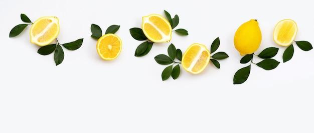 Limão fresco com folhas verdes em fundo branco.