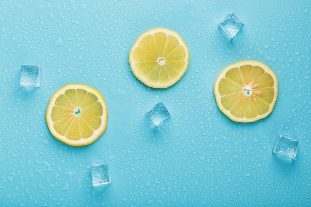 Limão fresco com gelo e gotas sobre um fundo azul