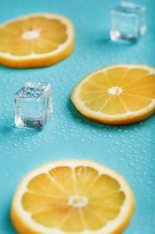 Limão fresco com gelo e gotas sobre uma mesa azul