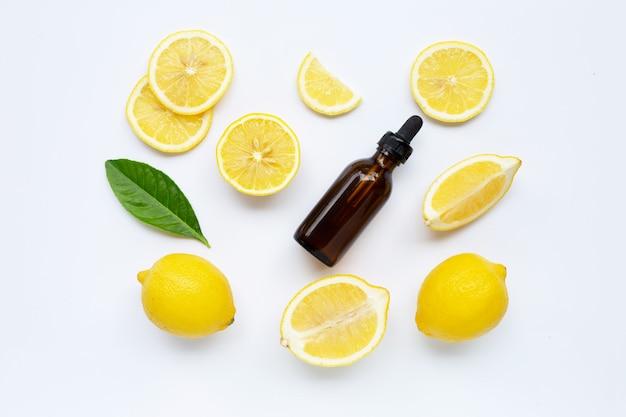 Limão fresco com óleo essencial de limão no fundo branco.