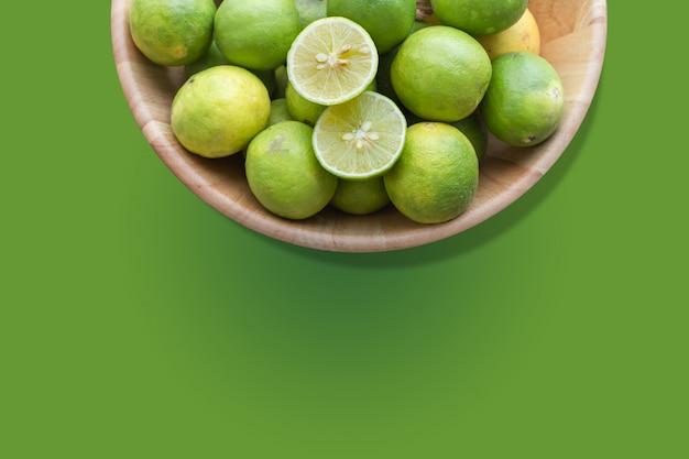 Limão fresco cortado no fundo verde isolado.
