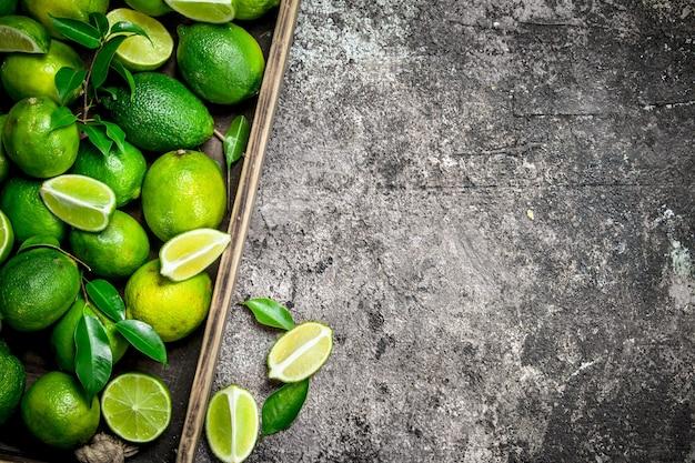 Limão fresco e fatias de limão maduro na bandeja. em fundo rústico
