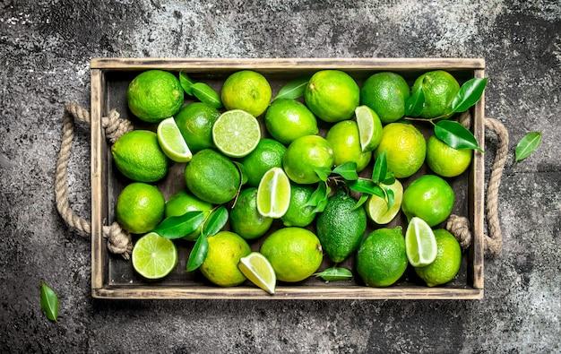 Limão fresco e fatias de limão maduro na bandeja. em superfície rústica