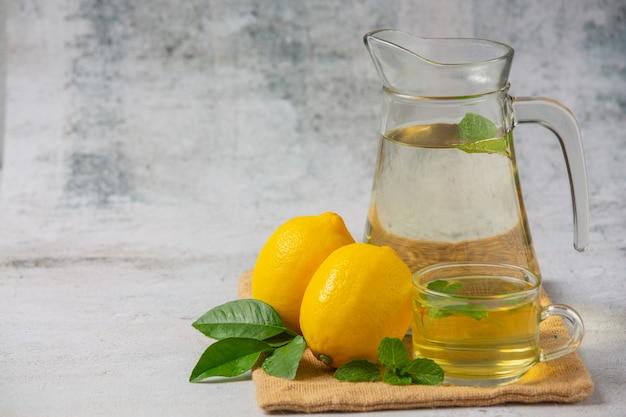 Limão fresco e suco de limão em uma jarra de vidro