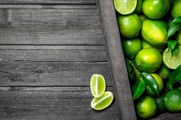Limão fresco e suculento na caixa. em fundo de madeira Foto Premium