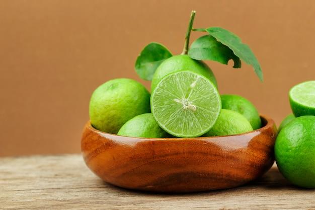 Limão fresco em tigela de madeira com fundo de madeira
