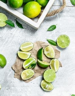 Limão fresco na bandeja e fatias de limão no papel. em fundo rústico