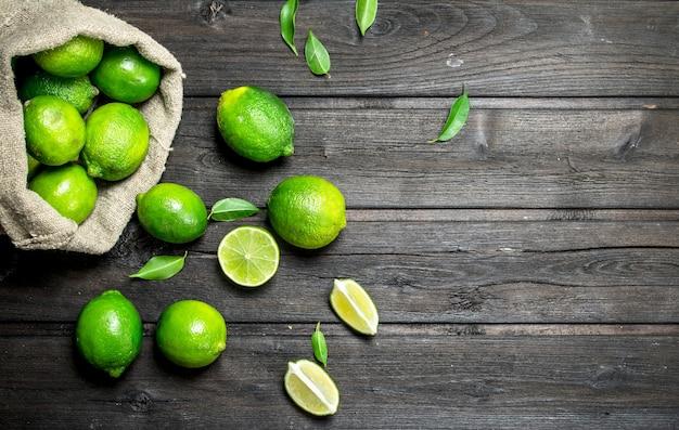 Limão fresco no saco e pedaços de limão suculento. em fundo de madeira