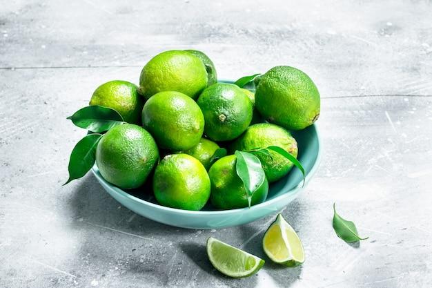 Limão fresco suculento com folhas em um prato. na mesa rústica Foto Premium