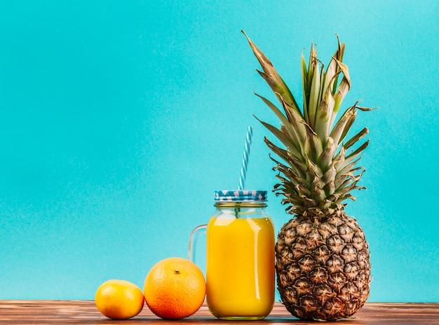 Limão; fruta laranja; pote de suco de abacaxi e suco com palha contra fundo turquesa