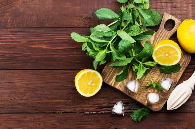 Limão, hortelã, gelo em uma tábua de madeira sobre um fundo de madeira