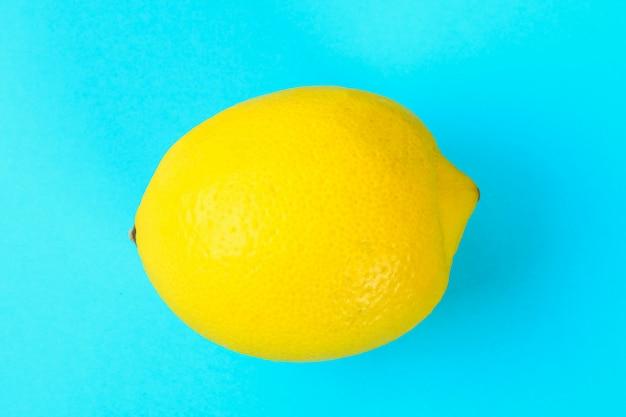 Limão inteiro amarelo em um fundo azul pastel.