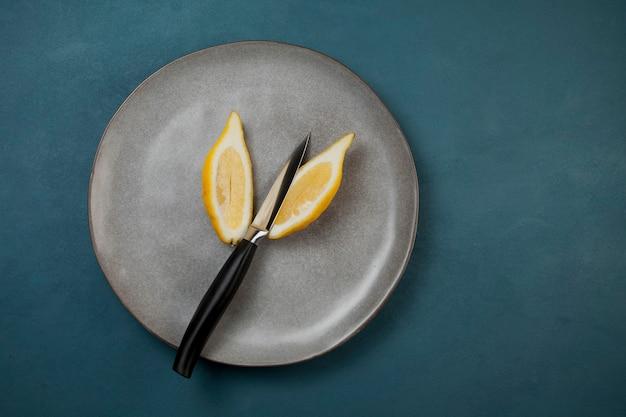 Limão longo e estreito em um prato cinza, cortado em duas partes com uma faca.