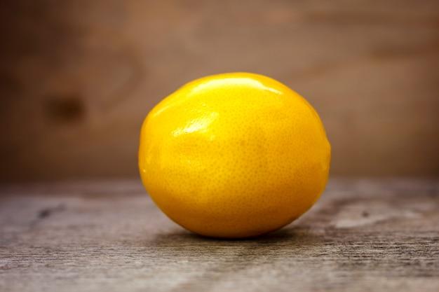 Limão maduro em uma mesa de madeira sobre um fundo marrom