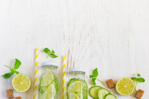 Limão, pepino, limonada de salsa em garrafas em um background branco