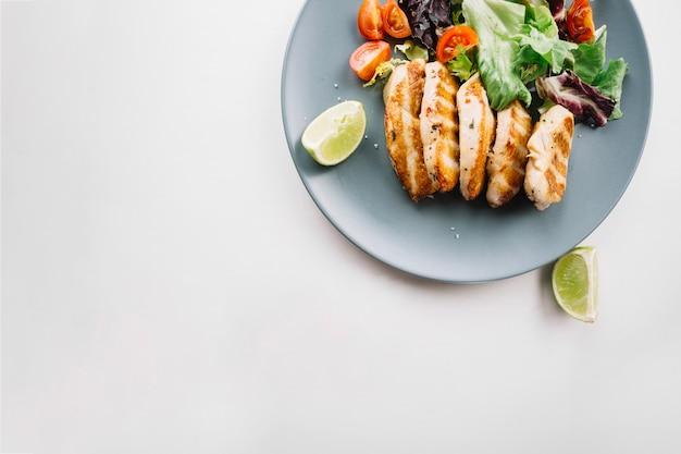 Limão perto de carne assada e salada