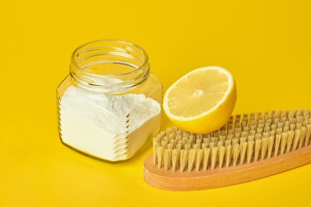 Limão refrigerante e pincel de madeira em fundo amarelo