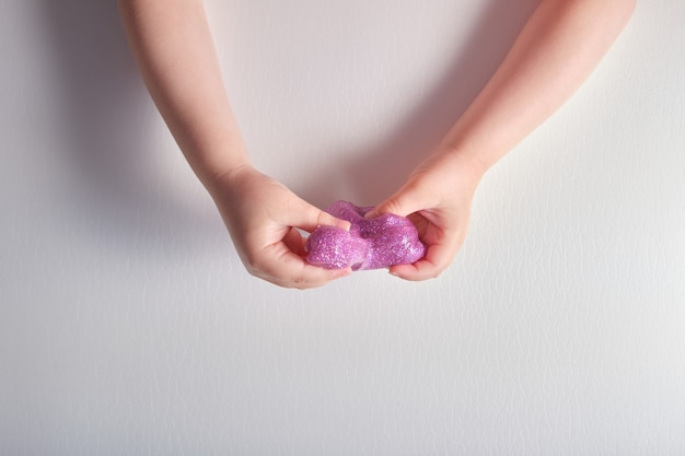 Limão rosa brilhante nas mãos de crianças em uma superfície cinza