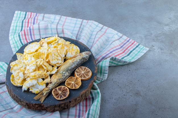 Limão seco, peixe e batatas fritas em uma placa sobre uma toalha, no fundo de mármore.