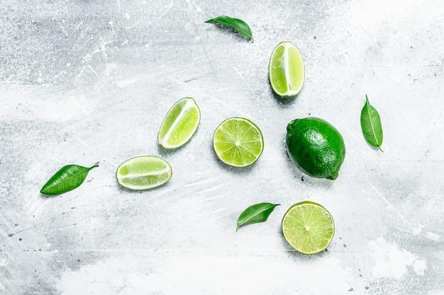 Limão suculento cortado e inteiro com folhas. sobre fundo branco rústico