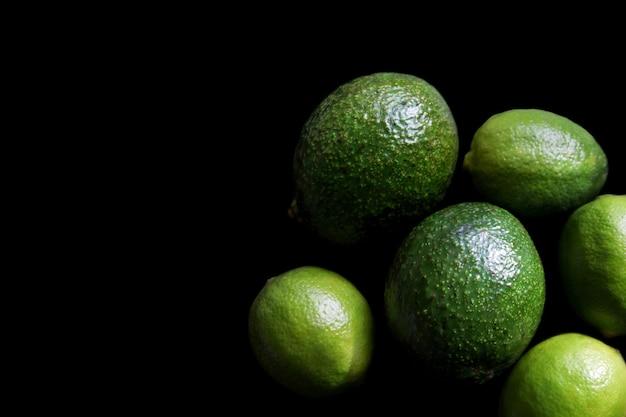 Limão suculento e abacate em um fundo preto