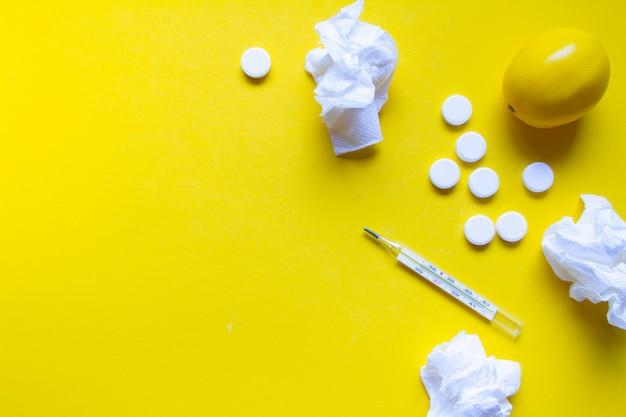 Limão, termômetro e comprimidos médicos brancos sobre fundo amarelo, tema de farmácia, tratamento e prevenção de vírus. conceito de saúde na temporada de resfriados.