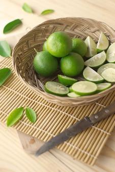 Limão verde com fatia verde do limão na cesta de bambu com faca e folhas.