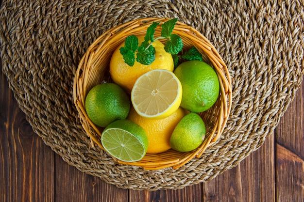Limas com limões, ervas em uma cesta de vime na mesa de madeira