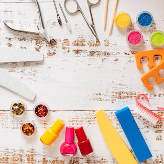 Limas para unhas, tesouras, alicates, lantejoulas e esmaltes em um fundo branco de madeira.