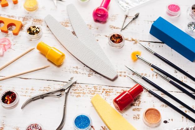 Limas, tesouras, alicates, lantejoulas e esmaltes para unhas em um fundo branco de madeira.