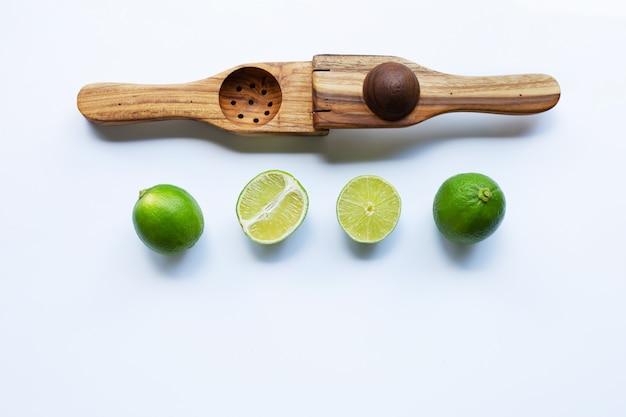 Limes com espremedor de lima de madeira em branco