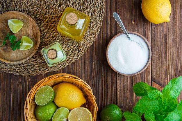 Limes com limões, ervas, bebidas, sal na cesta e prato na mesa de madeira