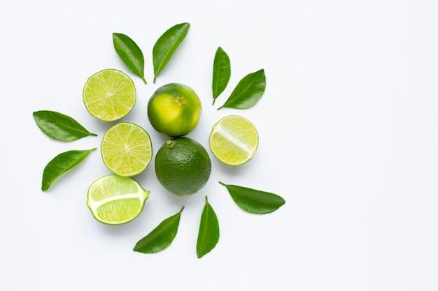 Limes frescos com folhas isoladas no branco