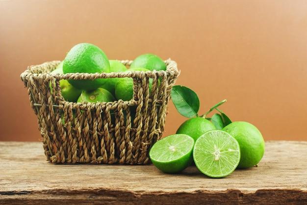 Limes frescos na cesta em um fundo de madeira