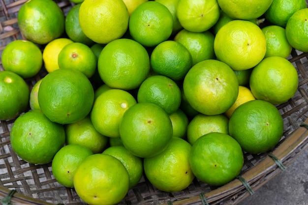 Limes verdes frescos em cesta de madeira para vender no mercado
