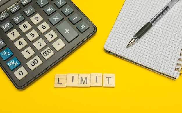 Limite de palavras feito com letras de madeira na calculadora amarela e moderna com caneta e caderno.