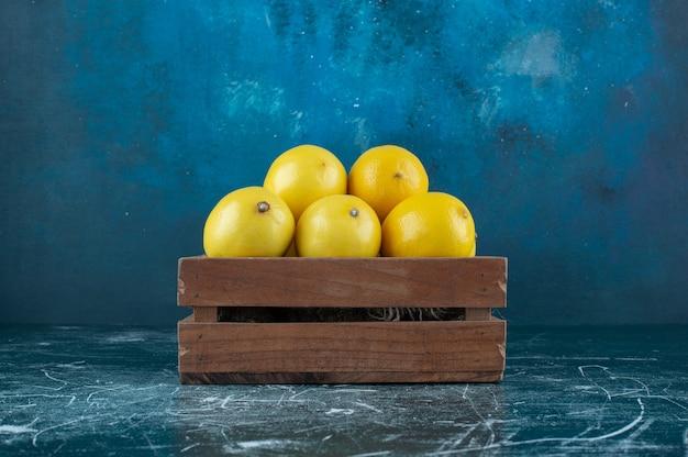 Limões amarelos azedos em caixa de madeira.