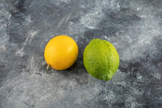 Limões amarelos e verdes em uma superfície de mármore.
