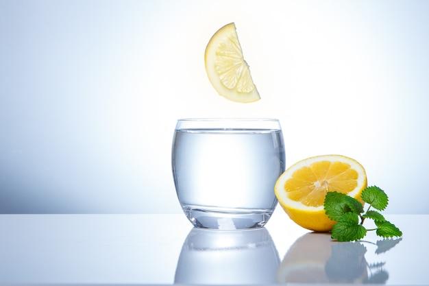 Limões amarelos em um copo e salpicos de água. comida saborosa e saudável. bebidas sazonais