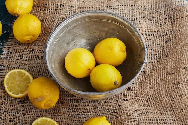 Limões amarelos em uma tigela metálica.