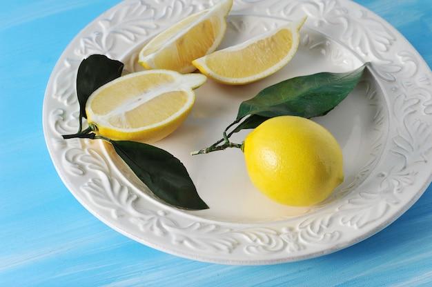 Limões amarelos frescos com folhas em um prato sobre fundo azul de madeira
