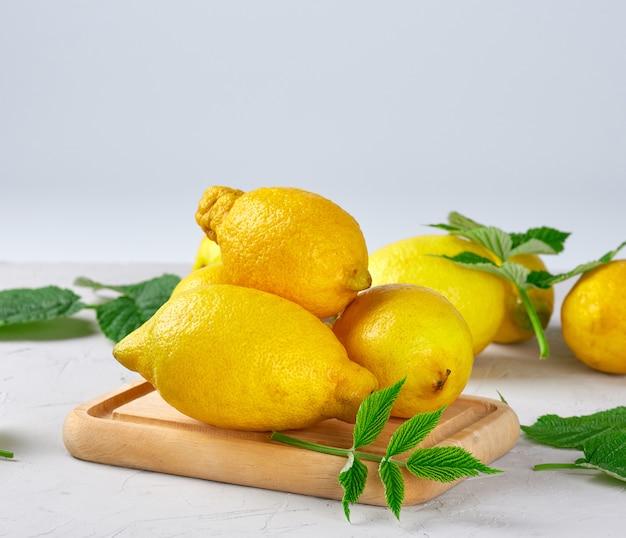 Limões amarelos inteiros maduros frescos, ingredientes para fazer bebidas de verão