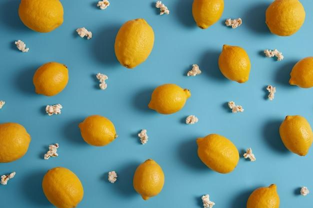 Limões amarelos maduros e pipoca doce ao redor. bela composição de frutas cítricas sobre fundo azul. deliciosa fruta tropical saudável com muitas vitaminas. conceito de nutrição. fechar-se
